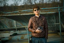 Free Man In Brown Leather Jacket Wearing Black Framed Sunglasses Holding Black Dslr Camera Standing In Front Of Black Steel Bar During Royalty Free Stock Image - 96793266