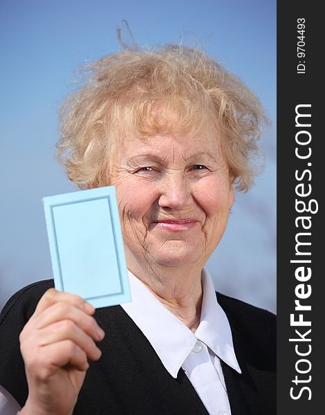 Aged woman holds card in hand