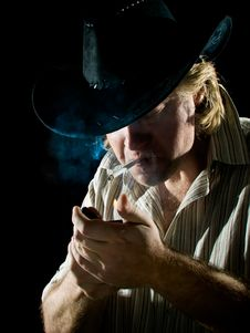 Man In Cowboy Hat Lights A Cigarette Royalty Free Stock Photo