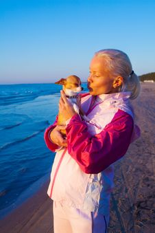 Young Woman With Her Dog On A Beach Royalty Free Stock Images