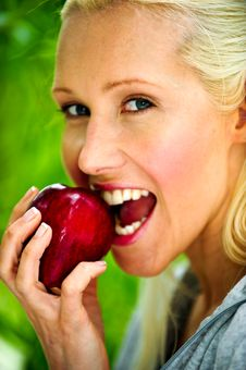 Free Beautiful Young Woman Enjoying A Healthy Red Apple Stock Photo - 9715660