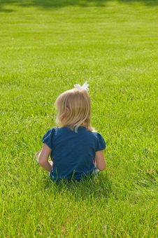 Little Girl Sitting In Grass Royalty Free Stock Photography
