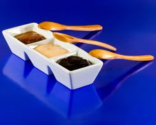 Sauces In Container With Spoons On Blue Background Royalty Free Stock Photos