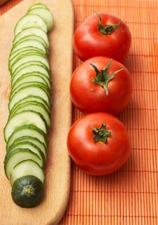 Red-ripe Tomatoes And Slices Of Cucumber Royalty Free Stock Photo