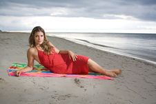 Attractive Girl Laying On A Towel With Red Dress Stock Photos