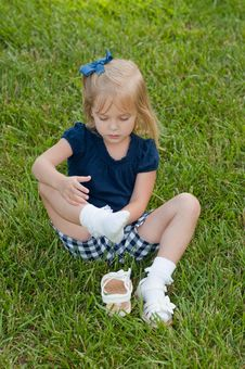 Free Little Girl Sitting In Grass Taking Off Shoes Royalty Free Stock Photos - 9833278