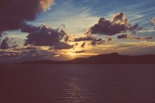 Free Faded Sunset Over Ocean With Land Royalty Free Stock Photos - 98351888