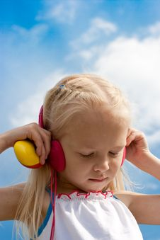 Little Blonde Girl With Red Earphones Royalty Free Stock Photos
