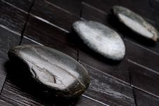Free 3 River Rocks On Black Wood Royalty Free Stock Photos - 9884088