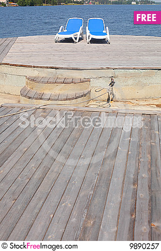 Chaise longues on the pier Stock Photo