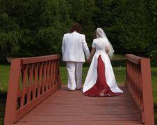 Bride And Groom Cross The Bridge Royalty Free Stock Photo