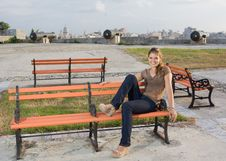 Free Girl Relaxing In A Orange Coloured Bench Stock Photos - 9906393