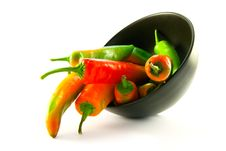Chillis Spilling Out Of A Black Bowl Royalty Free Stock Images