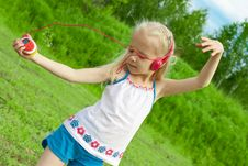Blonde Girl With Earphones Dancing Royalty Free Stock Images