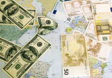 Dollars And Euro On A World Card Stock Images