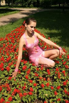 Pretty Girl Sitting Among Flowers Stock Photo
