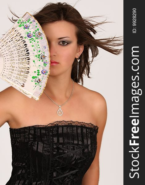 Girl with fan over her face