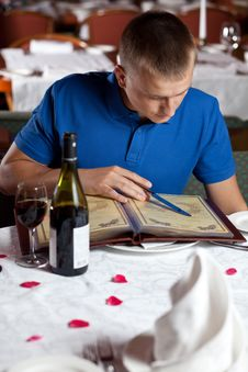 The Man In Cafe And Chooses Meal Under The Menu Royalty Free Stock Photos