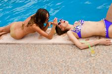 Free Girl Giving A Drink To The Other On The Pool Royalty Free Stock Image - 9967036