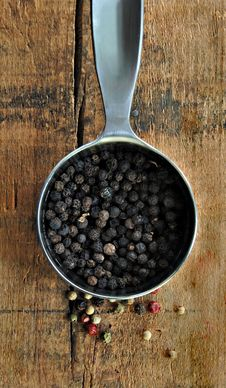 Black Peppercorns In A Metal Measuring Cup Stock Photo