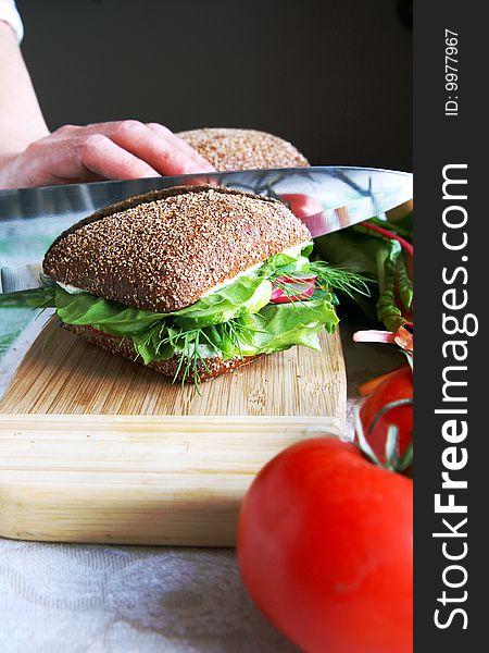 Dividing healthy rye bread sandwich in half