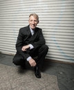 Free Businessman Squatting And Smiling Royalty Free Stock Image - 9984196